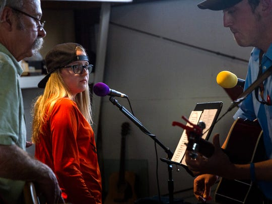 Kenzie Kannard, center, works on a song with Jim Kuzma, left, and Michael Stephens during The Imagine Band's rehearsal on Tuesday.