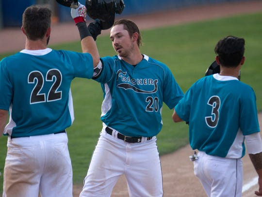 The Frackers' Matt Martin, center, is greeted at home plate by teammates Andrew Pratt, left, and Eddy Vasquez after hitting a two-run home run against the California Jays at Ricketts Park in Farmington.