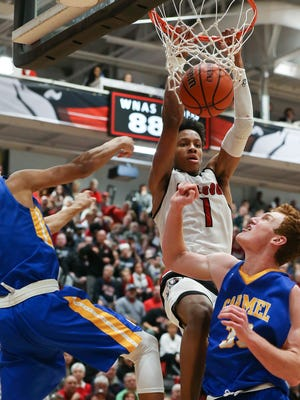 New Albany's Romeo Langford (1) dunks over Carmel's Eddie Gill (4) and John Michael Mulloy (33) during their game at New Albany High School.  New Albany edged Carmel 55-52.Dec. 20, 2016