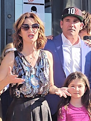 "Real estate mogul and celebrity business coach Grant Cardone, right, with his wife Elena and family, on the steps of Wake Up Pueblo, a business he built for the reality show ""Undercover Billionaire."""