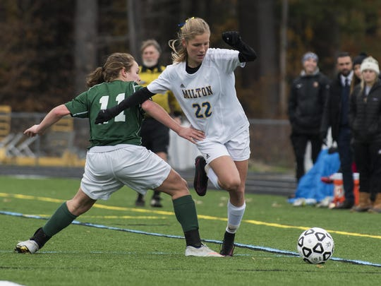 Milton's Tatum Shappy (22) gets past Montpelier's Lexie Drew (11) with the ball during the Division II girls soccer championship game between the Montpelier Solons and the Milton Yellowjackets at South Burlington High School on Saturday.