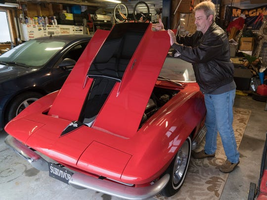 Chris Velfling lifts the hood of his 1967 Corvette.