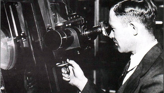 """On Feb. 18, 1930, Clyde Tombaugh discovered photographic evidence of Pluto (now designated a """"dwarf planet"""") at Lowell Observatory in Flagstaff, Arizona. In this 1930 image, Tombaugh uses the Zeiss Blink Comparator at the observatory. Tombaugh was born in Streator, Illinois."""