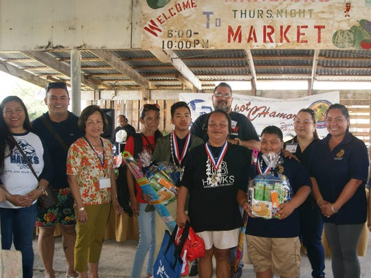 The GDOE Chamoru Studies Division held a Gerran Kadon Pika Competition (Hot & Spicy) on March 11, at Mangilao Night Market, one of several Island-wide Chamoru Month 2017 Activities. Category 2, 1st Place Winner, F.B. Leon Guerrero Middle School. Pictured: Judiah-Paul Santos and Wilson Tadeo. Pictured, from left: Mariann T. Lujan (F.B. Leon Guerrero Middle School, Assistant Principal), Robert Martinez, (F.B. Leon Guerrero Middle School, Principal), June R. Aguon (Grandmother), Melva Tadeo (Parent), Ron Fejeran (Judge), Queenie Ayuyu (Judge), Si–ora Dorianne Walker (F.B. Leon Guerrero Middle School, Chamoru Language Teacher), Si–ora Rufina F. Mendiola(Chamoru Studies & Special Projects Division, Administrator), and Si–ot Jimmy S. Teria (Chamoru Studies & Special Projects Division, School Program Consultant).