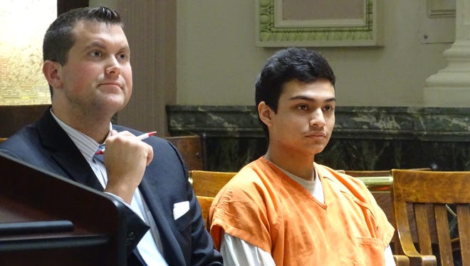 Angel Santos Ortiz, right, 18, of Brownsville, Texas, sits with his attorney, Adam Stone, before being sentenced Thursday to 11 years in prison.