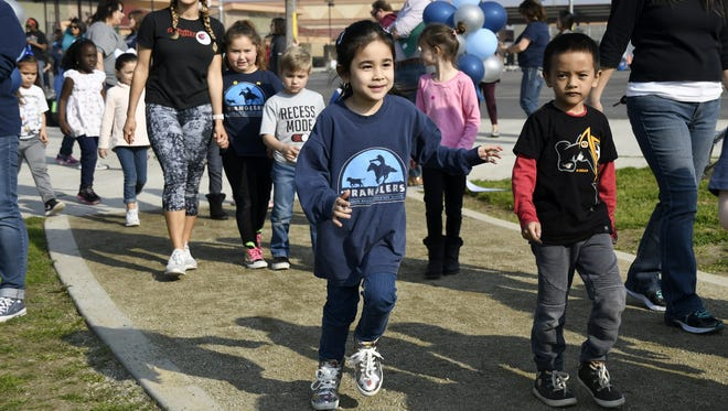 Shannon Ranch Elementary School students go for a run around their new track at a ribbon cutting on Wednesday afternoon.