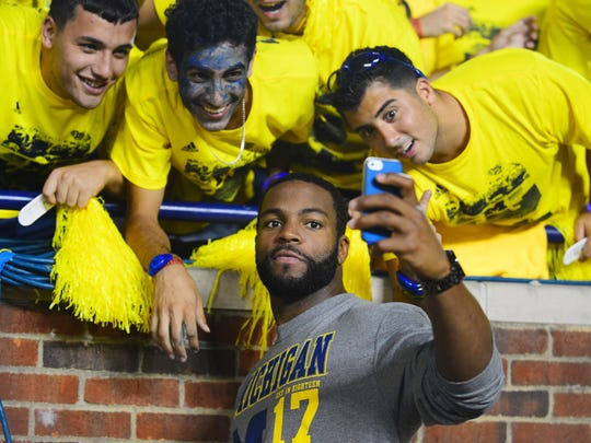Sep 7, 2013; Ann Arbor, MI, USA; Michigan Wolverines former player Braylon Edwards takes a picture with fans during the fourth quarter against the Notre Dame Fighting Irish at Michigan Stadium. Michigan Wolverines defeated Notre Dame Fighting Irish 41-30. Mandatory Credit: Andrew Weber-USA TODAY Sports