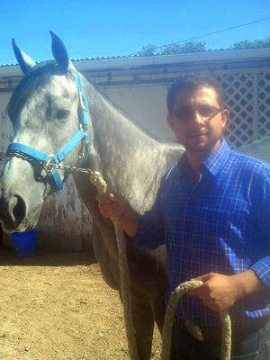Assistant trainer Juan Gonzales Jr. with Running Dragon.
