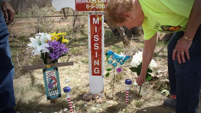 The grandmother of Brandon Lawson visits the cross that marks his last known location since he went missing on Aug. 9, 2013, outside of Bronte along US 277.