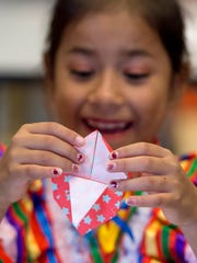 Yoselyn Arroyo, 7, folds origami during a lesson led by Tiffannie Hedin, external affairs analyst with Toyota Indiana, during the Kids World Gallery grand opening and ribbon cutting ceremony at the Koch Family Children's Museum of Evansville in Evansville, Ind., on Wednesday, Oct. 18, 2017. The new exhibit features areas representing Germany, Mexico, and Japan.