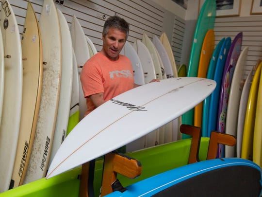 Mike Colombo, owner of Right Coast Surf Shop, shows