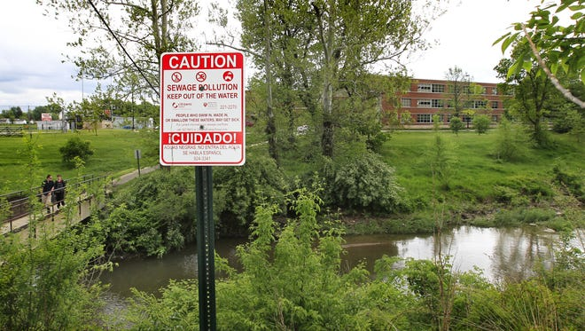 A sign cautions people of sewage pollution in Pleasant Run Creek near Indianapolis in this file photo.