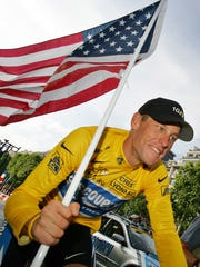 "In this July 24, 2005 file photo, Lance Armstrong carries the United States flag during a victory parade on the Champs Elysees in Paris, after winning his seventh straight Tour de France cycling race. In 2012, Armstrong decided to give up the battle against doping charges, saying ""enough is enough"" but acknowledging no wrongdoing."