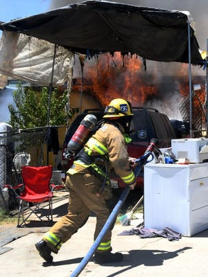 Firefighter approaches flames coming fro burning home on Naylor Street Thursday