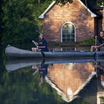 """Danny and Alys Messenger canoe away from their flooded home Tuesday after reviewing the damage in Prairieville, Louisiana.  Red Cross volunteers from throughout the country are heading to the area to help victims. The Greater Cincinnati-Dayton Region of the Red Cross is also seeking a new breed of volunteers -- """"virtual volunteers."""""""