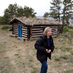 Jennifer Macy, an archaeologist with the BLM's Billings Field Office, hikes around the Will James cabin in the Four Dances Recreation Area, Thursday, May 14, 2015. (Casey Page/The Billings Gazette via AP)