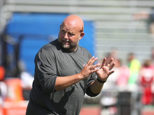 Bills offensive coordinator Brian Daboll helps with technique.