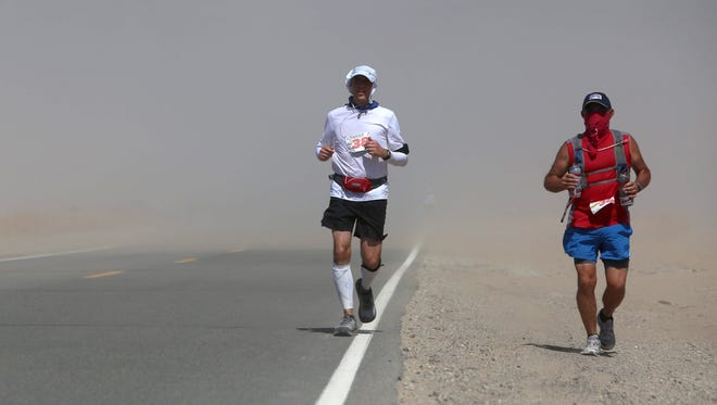 Cory Reese, left, and pacer Clair Coleman, a member of his support crew, run through a dust storm in Panamint Valley in Death Valley National Park Tuesday, July 19, 2016.