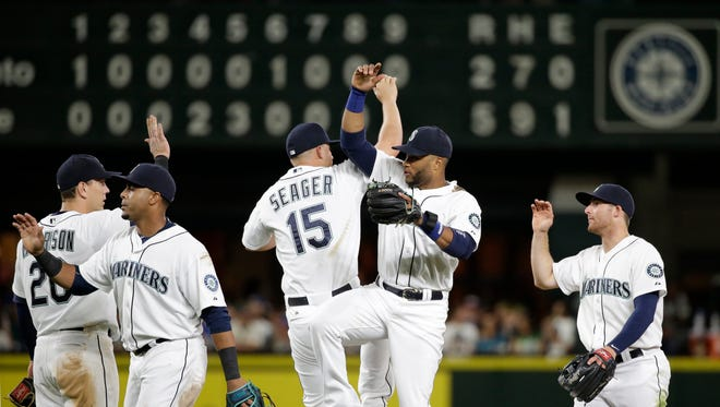 Seattle Mariners players celebrate after the team beat the Toronto Blue Jays in a baseball game Friday, July 24, 2015, in Seattle. The Mariners won 5-2.