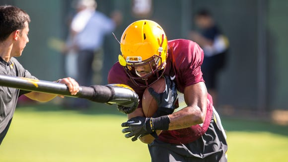 Arizona State wide receiver Eric Lauderdale (14) runs through a gauntlet holding the at football practice, Monday, August 4, 2014, at the Kajikawa Football Practice Field in Tempe. The Sun Devil's first game is against Weber State at home on Aug. 28.