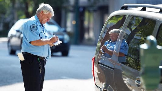 Parking enforcement officer Ralf Windham tickets a vehicle parked at an expired meter near Smith Park in downtown Jackson. A lawsuit filed against the city claims it is running what amounts to a debtors' prison for people who cannot pay fines levied against them.
