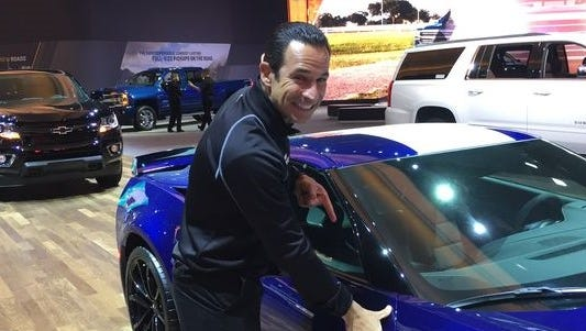 Helio Castroneves playfully puts his thumb print on a Chevrolet Corvette at the North American International Auto Show on Friday, Jan. 13, 2017 at Cobo Center in Detroit.