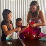 Viera resident Ingrid Houston and her daughters, Chloe and Sienna, wrap a gift to be delivered as part of the Reaching Out Holiday Fund program.