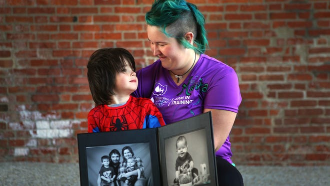 Western Hills resident Marsha White is running the Flying Pig half-marathon on behalf of Team in Training and her son, Connor, who passed away last year. White embraces her son, Sionn, while holding a family photo that was taken ten days before her son, Connor, passed away.