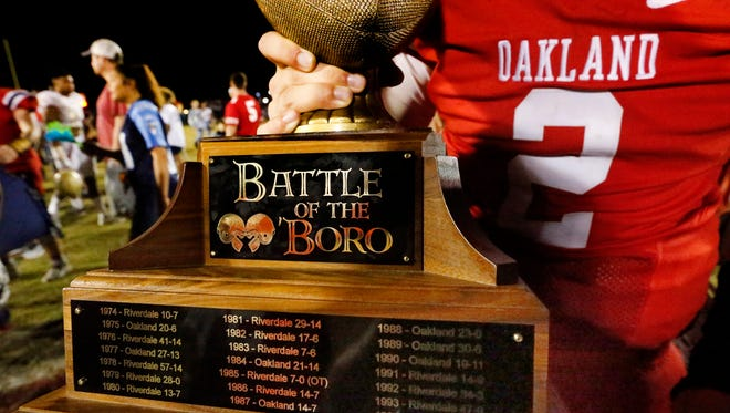 Oakland quarterback Brevin Linnell holds the Battle of the 'Boro trophy following a 43-14 win over Riverdale last season. The two teams will kick off for the 50th time Friday at Tomahawk Stadium.