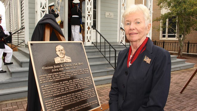 Anna Gibler unveils a memorial plaque in honor of her late husband, Col. John Gibler, during Friday's ceremony at Marion Military Institute. Alvin Benn/Special to the Advertiser.