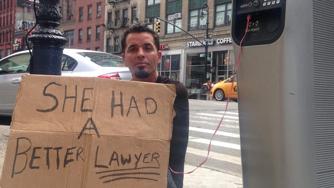 Matthew Kane charges his phone while panhandling at a Wi-Fi kiosk at 39th Street and Eighth Avenue in New York.