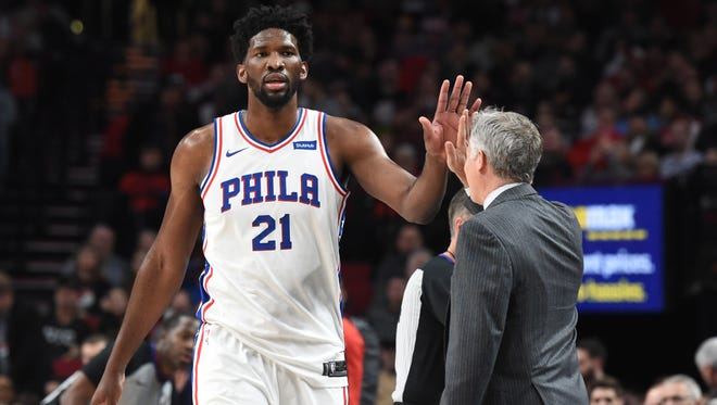 Philadelphia 76ers center Joel Embiid (21) is greeted with a high five from head coach Brett Brown during a game last month in Portland on Dec. 28. Despite a tough loss that night, the 76ers are on pace to meet expectations this season according to columnist Bob Cooney.