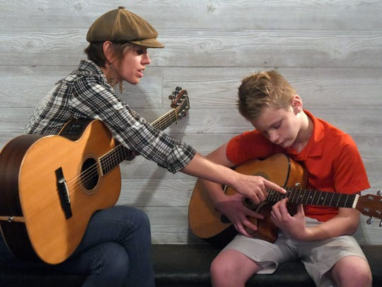 Andrea Wirth works with Logan Howard, 12, of Evansville during a guitar lesson at Honey Vinyl Music Studio in Newburgh.  Wirth and Melanie Bozsa of The Honey Vines offer songwriting, guitar and vocal lessons at the studio.