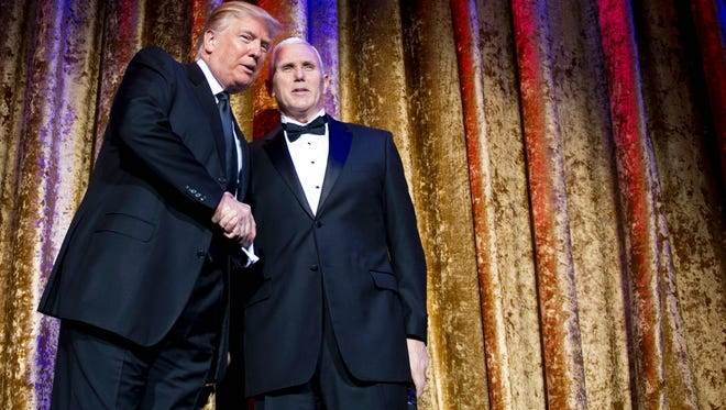 "US President-elect Donald Trump (L) shakes hands with Vice President-elect Mike Pence (R) as they attend the Chairman's Global Dinner,  a black-tie, invitation-only dinner aimed at introducing foreign diplomats to the team tasked with implementing the ""America First"" policies of the next administration, in Washington, DC on January 17, 2017."