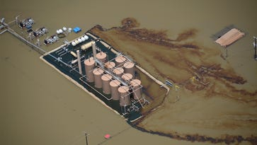 Oil runs from a production site on the Lower Trinity River on June 8 during flooding. The Texas Railroad Commission says it ensured the spill was cleaned up, but others are skeptical.