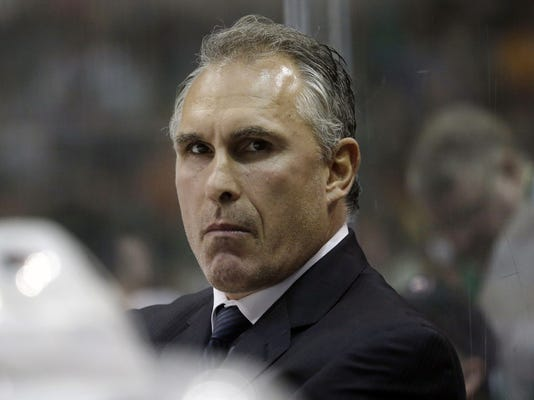 """FILE - In this Oct. 18, 2014, file photo, Philadelphia Flyers head coach Craig Berube looks on from the bench during the first period of an NHL hockey game against the Dallas Stars in Dallas. Berube played in the NHL from 1986-2004 and accumulated 3,149 penalty minutes, seventh of all time. He hasn't been a pushover on the bench, either. """"When he gets barking, you don't want to be making eye contact with him too much,"""" Flyers forward Wayne Simmonds said. (AP Photo/LM Otero, File)"""