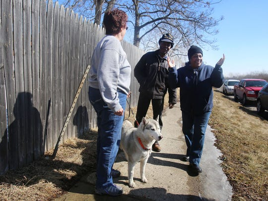 Theresa Pryzbyisk, left, is so happy to show Pamela and Bill Henry that she has just found her dog Mandy, a 6-year-old Siberian Husky, that was missing since Friday after her van was stolen in Ann Arbor. The Henrys were among those who spotted her today and were trying to capture her with other searchers helping  Theresa and her husband Bill Pryzbyiski who drove from the Chicago area to help search for the dogs Monday, March 9, 2015.  They captured the husky along the Lodge service drive north of the Livernois exit and south of San Juan in Detroit.