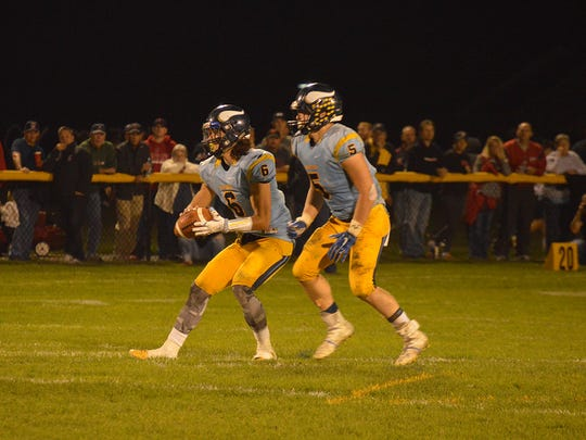 River Valley quarterback Josh Ellwood takes the snap with running back Tyler Spears in the backfield Friday night against Pleasant. The Spartans won 27-14.
