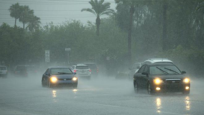 Vehicles drive through heavy rain on Indian School Road in Phoenix  on Aug. 5, 2016.