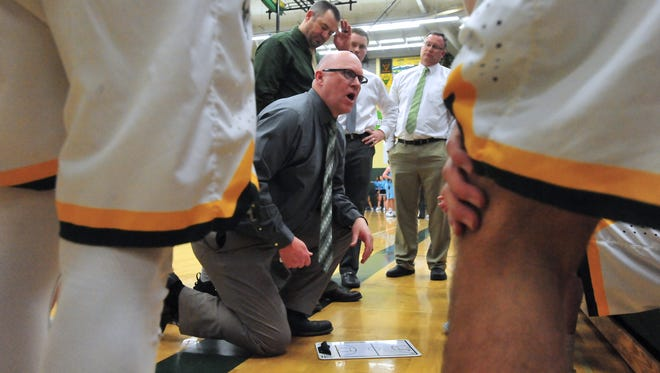 CMR coach John Cislo huddles with his players in a timeout during the boys crosstown basketball game on Thursday in the CMR Fieldhouse.