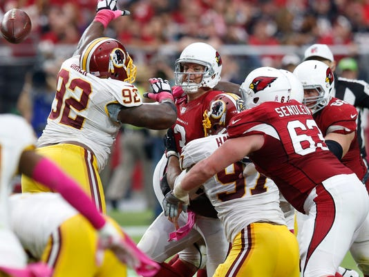 Arizona Cardinals quarterback Carson Palmer, center, gets a pass off as Washington Redskins nose tackle Chris Baker (92) pressures during the second half of an NFL football game, Sunday, Oct. 12, 2014, in Glendale, Ariz.(AP Photo/Ross D. Franklin)