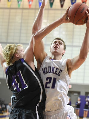 Waukee's Anthony Nelson puts up a shot over Johnston's Regen Siems during the first half of Friday's Class 4-A substate semifinal at Waukee Fieldhouse. Nelson had 22 points and 13 rebounds in the Warriors' 48-27 win.