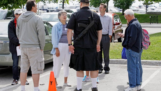 Bill Polster of Sheboygan Falls carries a modified civilian AK-47 semi-automatic weapon before the Walk with Walker event Friday at Deland Park in Sheboygan. Polster did not carry his weapons during the walk.
