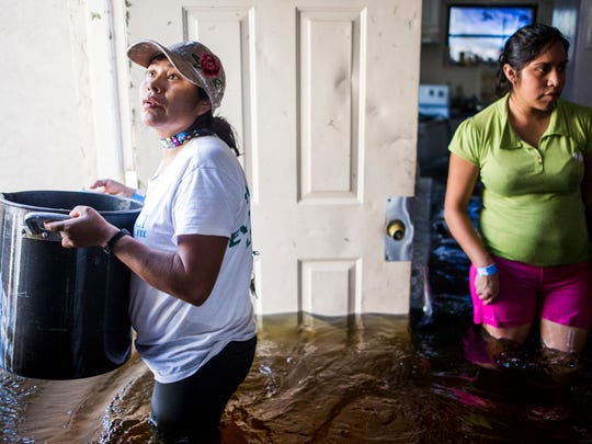 Basilica Ventura, left, and her niece, Nayeli Vasquez, right, carry the last salvageable valuables out of their flooded home on Quinn Street after Hurricane Irma in Bonita Springs on September 12, 2017.