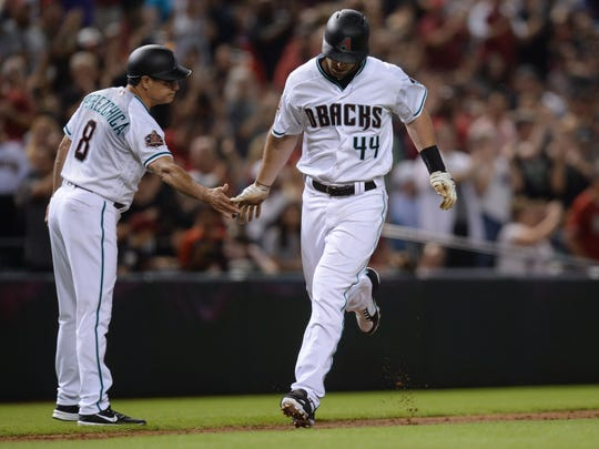 Arizona Diamondbacks first baseman Paul Goldschmidt (44) slaps hands with third base coach Tony Perezchica (8) after hitting a solo home run against the New York Mets during the first inning at Chase Field.