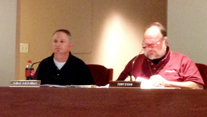 School Board members Mike McMillan and Tony Egan listen during a presentation on Tuesday.