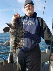 Jim Holmberg, Bayville, with a sea bass he landed on