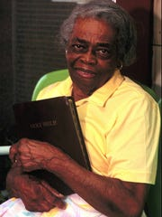 Oseola McCarty sits on the front porch of her home, holding her Bible July 1995 Hattiesburg American file photo. McCarty donated $150,000 to the University of Southern Mississippi from earnings she received from ironing and cleaning clothes.