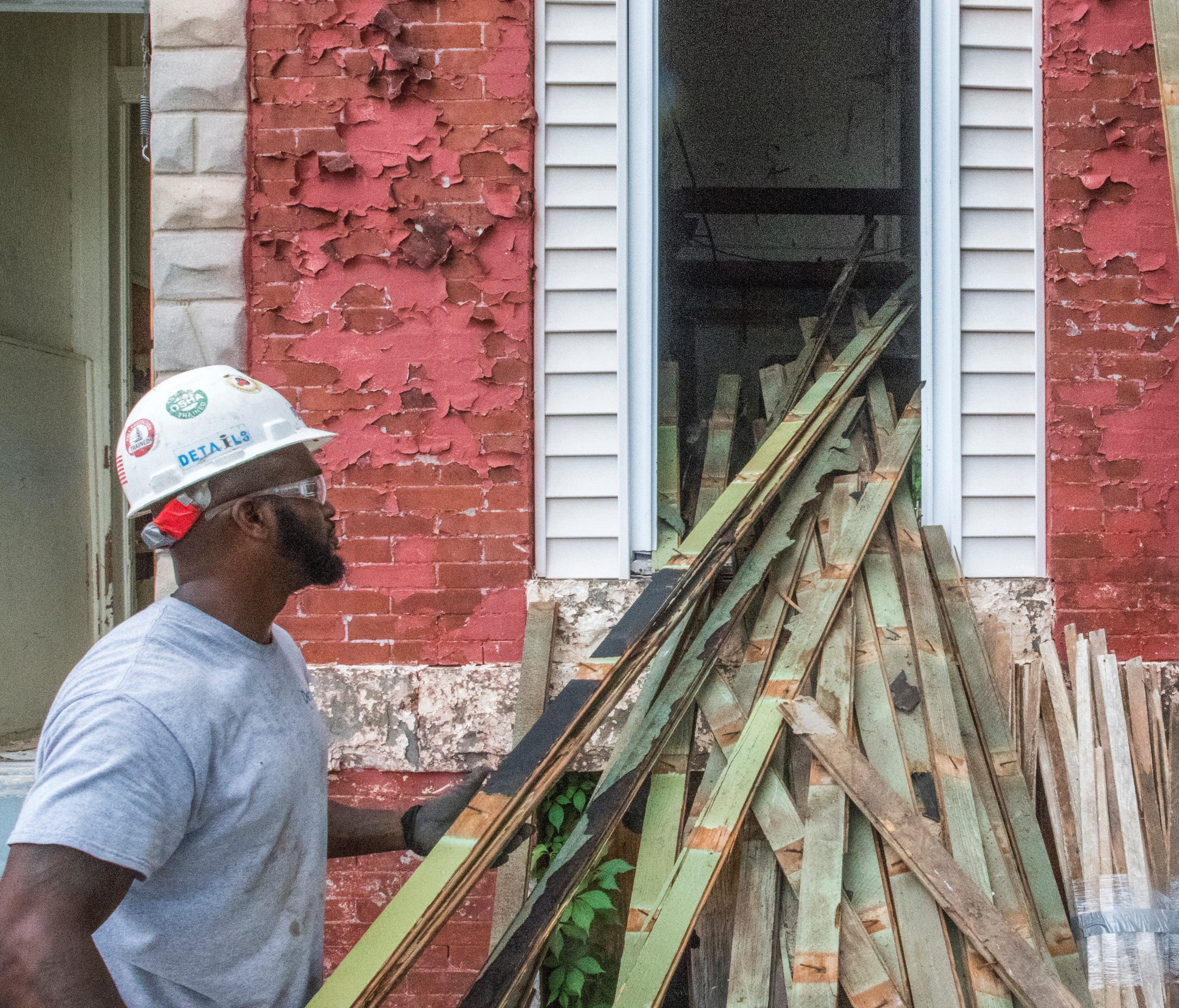 Working for the Humanim company, Details, Damon Toogood stacks planks of flooring outside of an abandoned East Baltimore row home.  The U.S. Forest Service and the non-profits have teamed up with the upscale furniture retailer Room & Board to put ex-