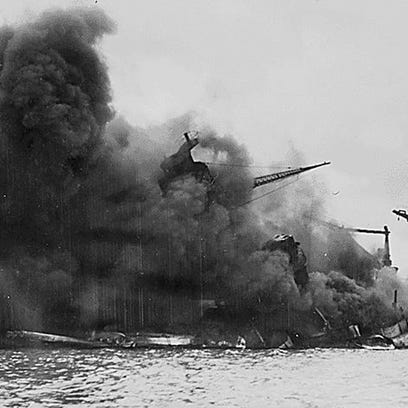 The USS Arizona burns after the Japanese attack on